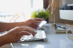 网上付款,拿着信用卡和使用巧妙的电话的男性手为网上购物 免版税图库摄影