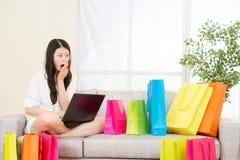 网上购物的亚洲妇女感受惊奇与计算机 库存照片