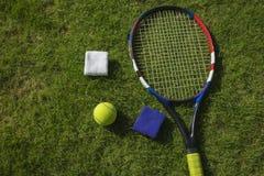 网球、球拍和袖口在草地研了在阳光下 库存图片