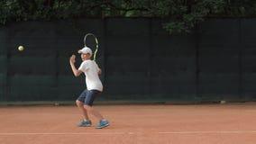 网球体育精神,集中和集中于比赛和球拍的雄心勃勃的儿童男孩打在红色法院的球 影视素材