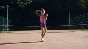 网球制服的年轻女人走在法院的后面观点的 影视素材