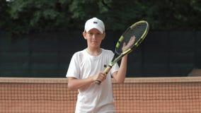 网球员有球拍的少年男孩画象在有竞争精神的手上在法院 股票录像
