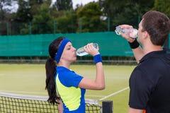 网球员饮用水夫妇在室外的比赛以后的 库存照片