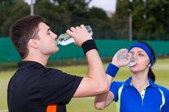网球员饮用水运动夫妇在比赛以后的  免版税库存照片