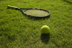 网球和球拍在绿草领域地面 免版税库存照片