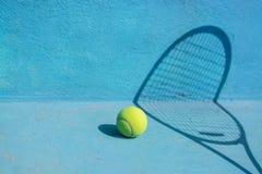 网球和球拍在蓝色法院 概念查出的体育运动白色 库存照片