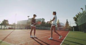 网球场两俏丽的夫人,准备好网球比赛,打的手和开始比赛 股票视频