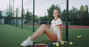 网球场的一个白肤金发的逗人喜爱的夫人,穿着美丽的网球衣服和使用与在前面的网球 影视素材
