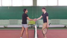 网球场的两个年轻适合的人来离栅格较近和握手 影视素材