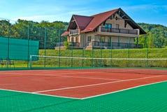 网球场,美丽的瑞士山中的牧人小屋在后面和围拢由树和小山 免版税库存照片
