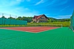 网球场,美丽的瑞士山中的牧人小屋在后面和围拢由树和小山 库存图片