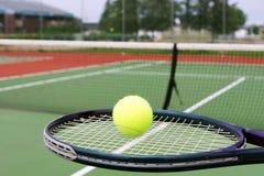 网球拍和球在法院 免版税库存图片