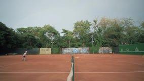 网球比赛、体育对手青年期男孩和女孩通过在开赛的网互相打在法院和通行证球的网球 影视素材