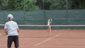 网球比赛,有互相击中在球通行证的兢争者的体育球员青年期男孩球拍通过网在法院 股票视频