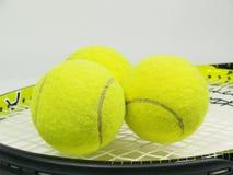 网球火箭和三个球 免版税库存图片
