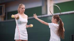 网球课的过程在度假区 教年轻女运动员的女性家庭教师使用 体育成套装备的女孩 股票录像