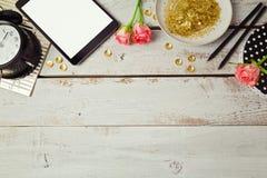 网站与数字式片剂和玫瑰色花的倒栽跳水设计在木桌上 在视图之上 免版税库存照片