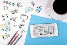 网站和流动app发展概念 手机和咖啡杯在白色办公桌上 库存图片