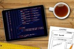 网站wireframe剪影和编程的代码在数字式片剂 图库摄影