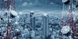 网络和互联网技术在城市 与都市风景和网络线的电信塔 免版税图库摄影
