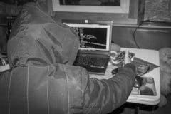 网络战争,有发动黑客攻击的膝上型计算机的黑客 图库摄影