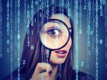 网络罪行概念监视  看通过放大镜和计算机二进制编码背景的好奇妇女 库存照片
