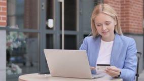 网络购物通过年轻女实业家坐室外