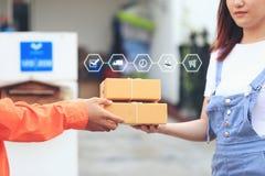 网络购物,接受小包的妇女从带来一些包裹的送货人在家,运输和邮政局概念 库存照片