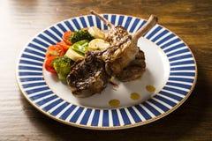 罕见的油煎的放在架子上的羊羔与菜的 免版税库存图片