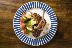 罕见的油煎的放在架子上的羊羔与菜的 库存图片