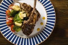 罕见的油煎的放在架子上的羊羔与菜的 图库摄影