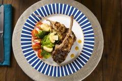 罕见的油煎的放在架子上的羊羔与菜的 免版税库存照片