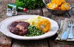 罕见的牛排用土豆泥、绿豆和煮沸的玉米 库存照片