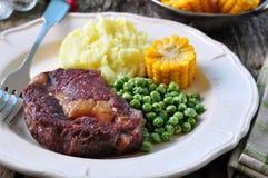 罕见的牛排用土豆泥、绿豆和煮沸的玉米 图库摄影