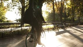 罕见的观点的黑便服的,骑自行车的耳机一年轻人由有吉他的被铺的城市公园在黑色 股票录像