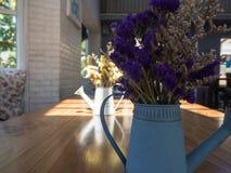 紫罗兰和黄色烘干了在蓝色罐子喷壶的花在木头 免版税库存照片
