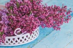 紫罗兰色丁香花束在装饰紫罗兰色盘子的 库存照片