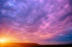 紫罗兰色日落的照片与云彩和太阳的 免版税库存图片