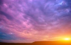 紫罗兰色日落的照片与云彩和太阳的 库存照片