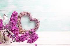紫罗兰色淡紫色花、装饰心脏和灯笼在白色木头 免版税库存照片