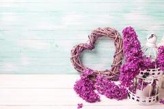 紫罗兰色淡紫色花、装饰心脏和灯笼在白色木头 库存照片