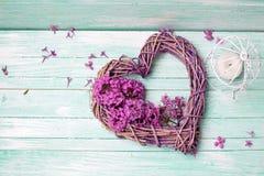 紫罗兰色淡紫色花、装饰心脏和灯笼在绿松石 库存图片