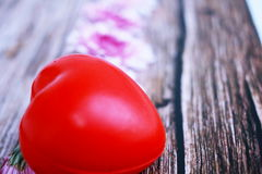 紫罗兰色花和红色心脏在葡萄酒木表上 库存照片