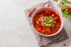 罗宋汤,在一个木碗的甜菜根汤用在轻的背景的新鲜的草本 免版税库存图片