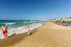 罗希姆诺,海岛克利特,希腊, - 2016年6月23日:与人的城市海滩在希腊城市罗希姆诺和两个男孩笑和playi 库存照片