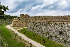 罗得岛和护城河中世纪墙壁在多云天空,希腊下 免版税库存图片