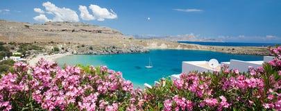 罗得斯 Lindos主要海湾看法与游艇、桃红色花、天蓝色的水和白色房子的 免版税库存照片