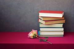 罗斯和堆在桌上的书与一张红色桌布 库存图片