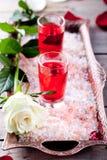 罗斯在小玻璃的味道利口酒在桃红色盐 免版税库存照片