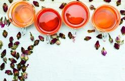 罗斯在白色背景的茶和花瓣 免版税图库摄影